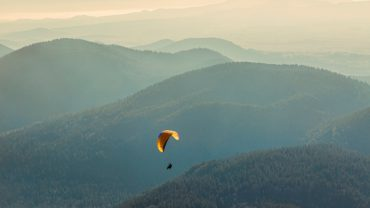 A man paragliding over a beautiful autumn evening landscape in the Volcanic Central Massif in France.