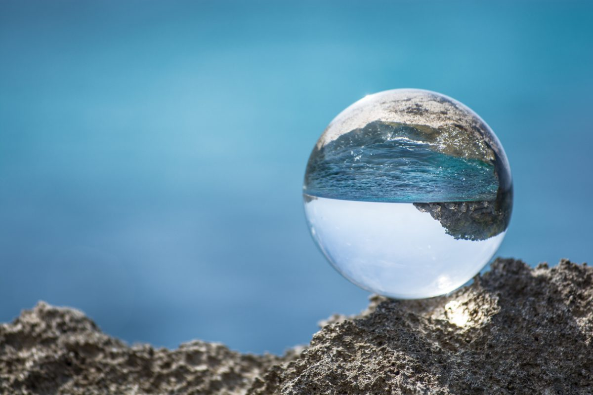 Glaskugel liegt auf einen Felsen vor dem Meer als Metapher für aufsichtsrechtliche Entwicklungen für das Zinsänderungsrisiko im Anlagebuch (IRRBB)