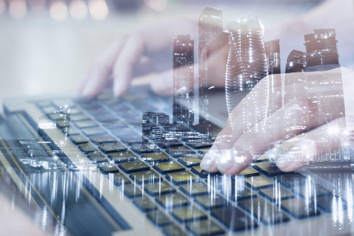 Tastatur, in die eingetippt wird vor transparenter Großstadt als Metapher für DD und MiFID II – Regulatorische Anforderungen mit großem Einfluss auf das Vertriebsmodell von Banken und Versicherungen