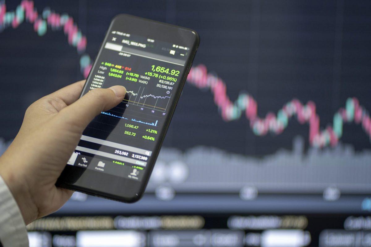 """Blick über das Smartphone auf Kurse als Metapher für den Artikel """"Zinsänderungsrisiko im Anlagebuch (IRRBB)"""""""