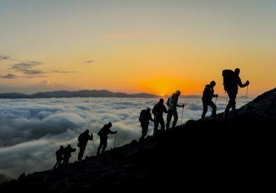 Silhouetten von Bergsteigern, die einen Gipfel erklimmen