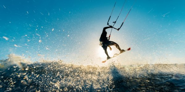 Image of a surfer doing an amazing jump and splashing water in front of the sunset at the sea