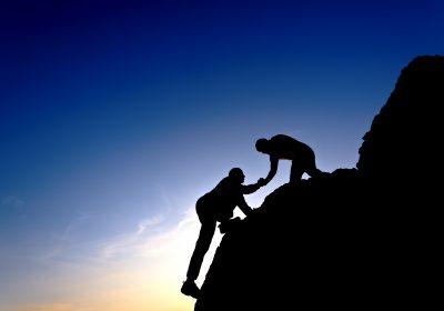 Zwei sich helfende Bergsteiger als Metapher für Fusionen von Regionalbanken