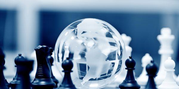 Grafische Darstellung eines Schachbrettes, in dessen Mitte die Weltkugel liegt, als Metapher für Step-In-Risiken