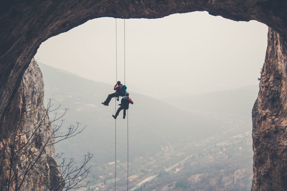 2 Kletterer die sich an der Wand herunterlassen als Metapher für neue Leitplanken für die Risikotragfähigkeit