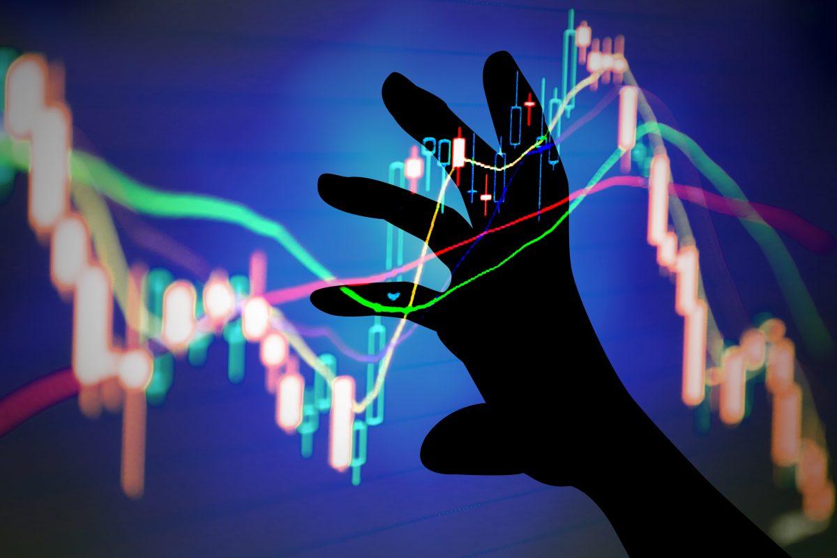Menschliche Hand die Kurvendiagramme lenkt als Metapher für inancial Reporting – integrierte, effiziente Lösungen