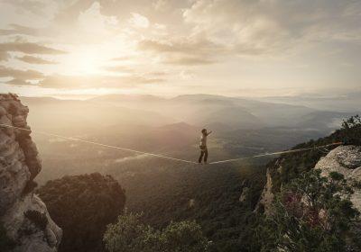 Seiltänzer zwischen zwei Bergen als Metapher für Risk-Governance-Self-Assessment