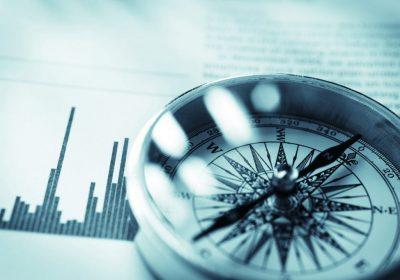 Close-up eines Kompasses vor Aktienmarkt-Daten als Metapher für Private Banking Deutschland 2018