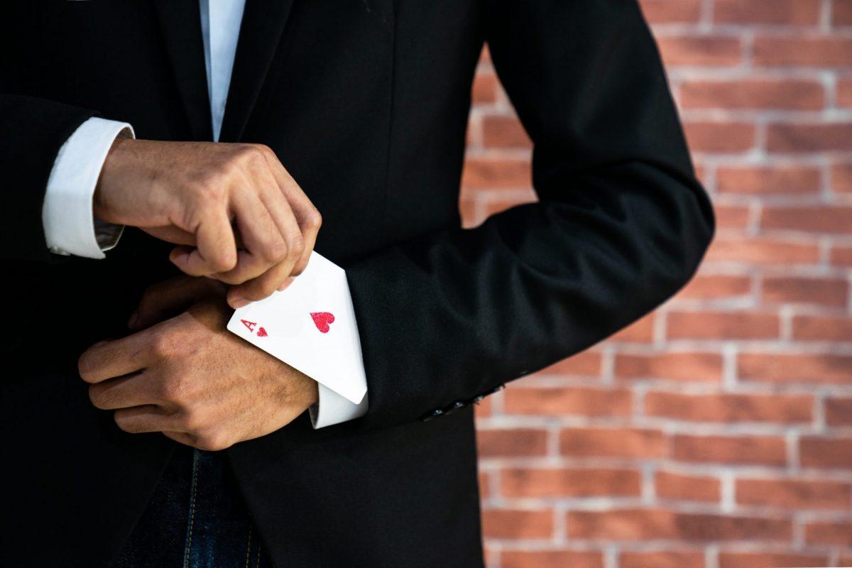 """Abstraktes Bild eines Geschäftsmann der ein Pik Ass aus dem Ärmel zabuert als Metapher für """"Open banking poker—Winner takes all"""""""