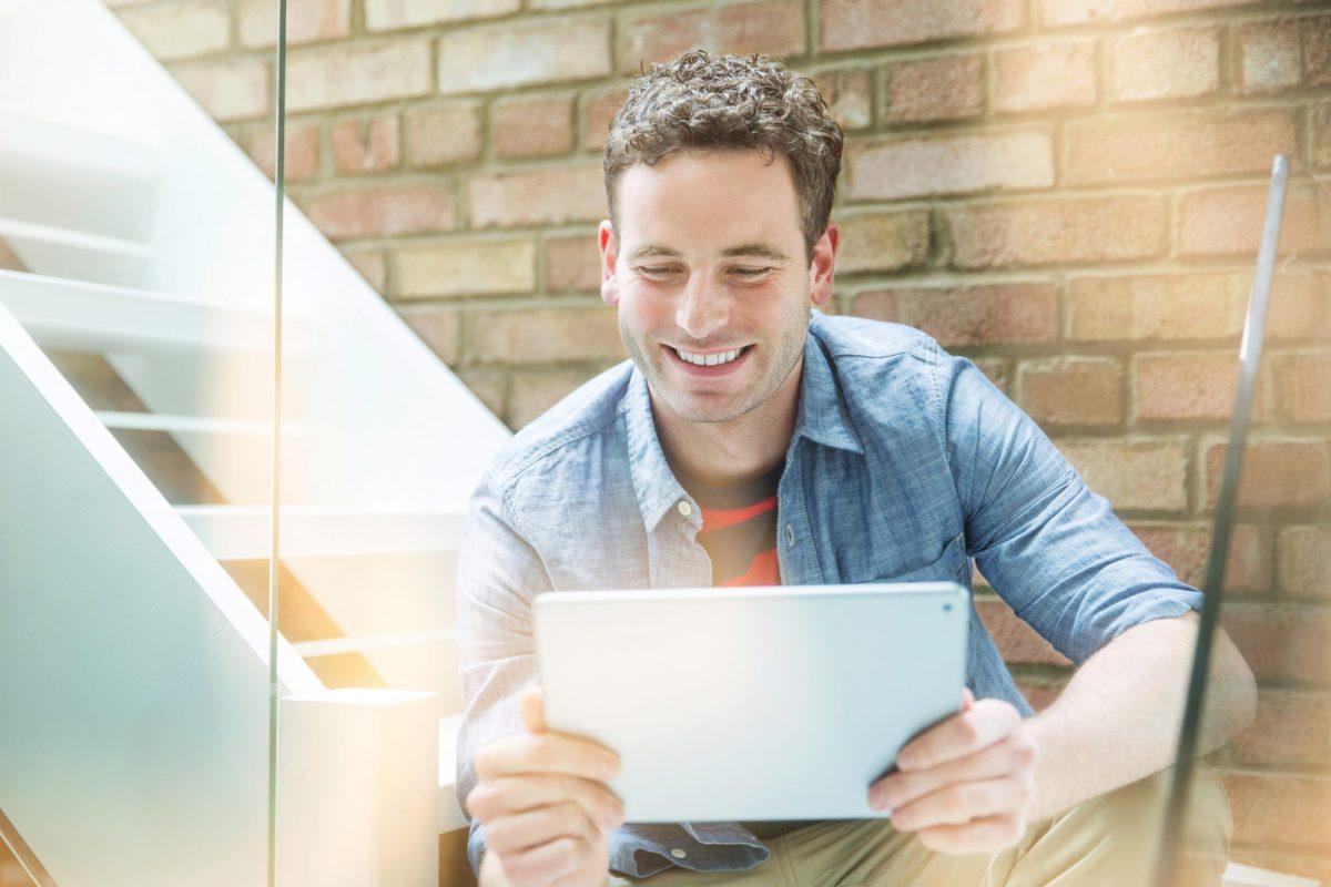 Junger Mann der Freude an digitalen Inhalten hat als Metapher für das Webinar auf dem BankingHub