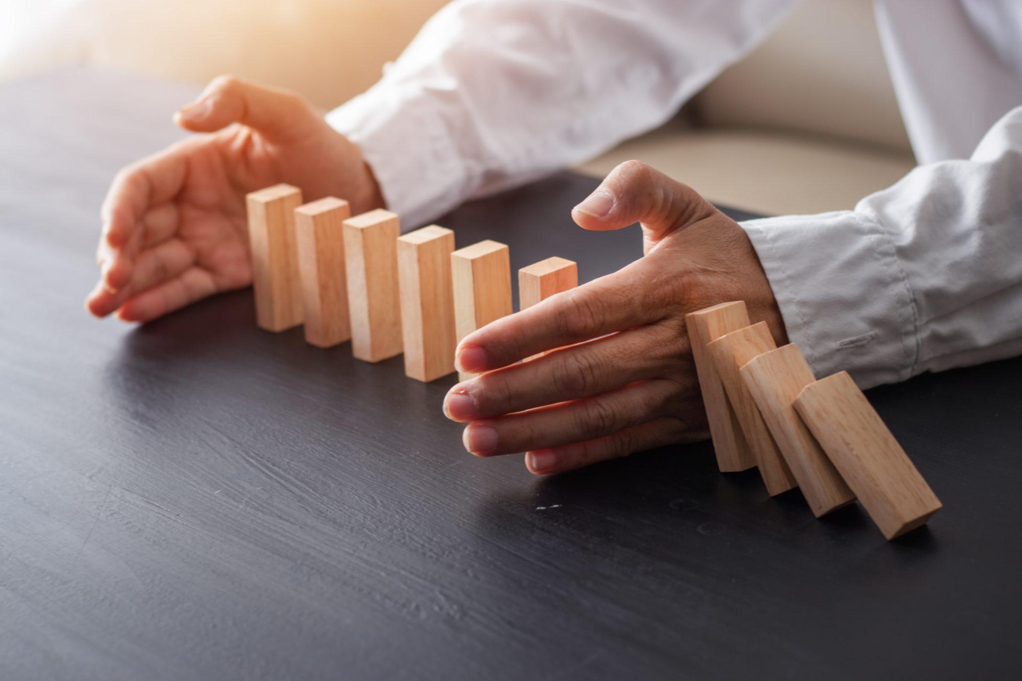 """Mann hält Dominosteine vor dem Fallen als Metapher für """"Corona – Handlungsprogramm Banksteuerung und Treasury in Regionalbanken"""""""