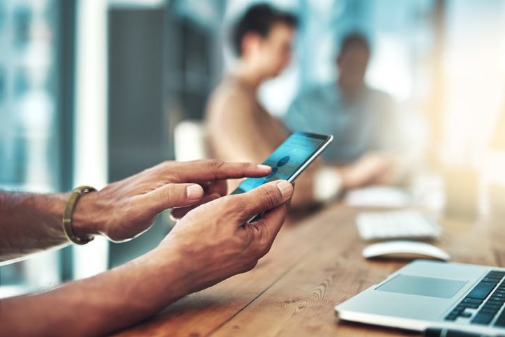 """Mann der sich über Smartphone einloggt als Metapher für """"Portale im Firmenkundenbanking"""""""