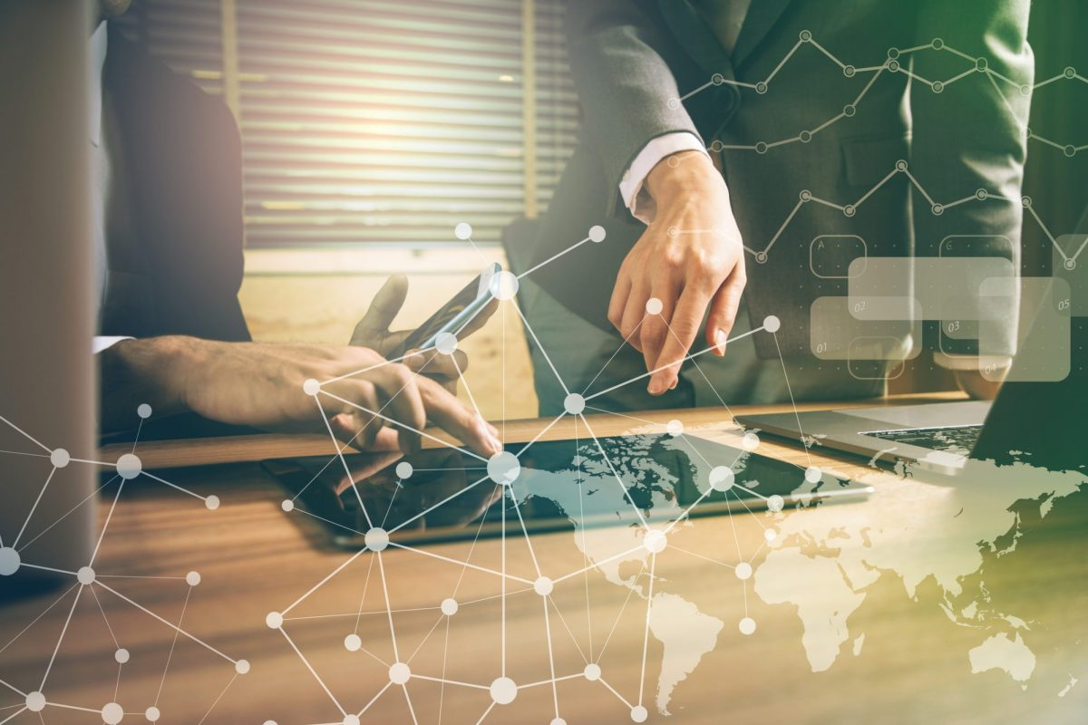 """Businessleute, die Blick auf Weltkarte und Entwicklungen werfen als Metapher für """"Fusions- und Übernahmeserie im Payment-Markt"""""""