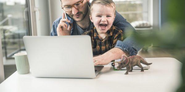 """Vater mit Kind auf dem Schoß am Notebook und Handy als Metapher für """"Mit Stress im Homeoffice entspannt umgehen"""""""