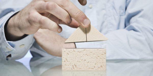 """Person die Haus baut als Metapher für Bausparen im Artikel """"Portale, Plattformen und Ökosysteme in der Bausparbranche"""""""