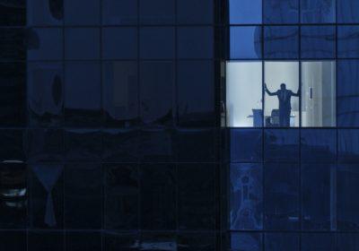 """Mann blickt in die Dunkelheit vom Bankentower als Metapher für """"Alle Artikel zur Covid-19-Krise im Überblick"""""""