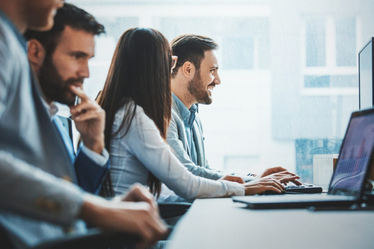 """Banking-Team betrachtet gespannt Entwicklungen am Notebook als Metapher für den Artikel """"EBA-Leitlinien: Kreditvergabe und -überwachung"""""""