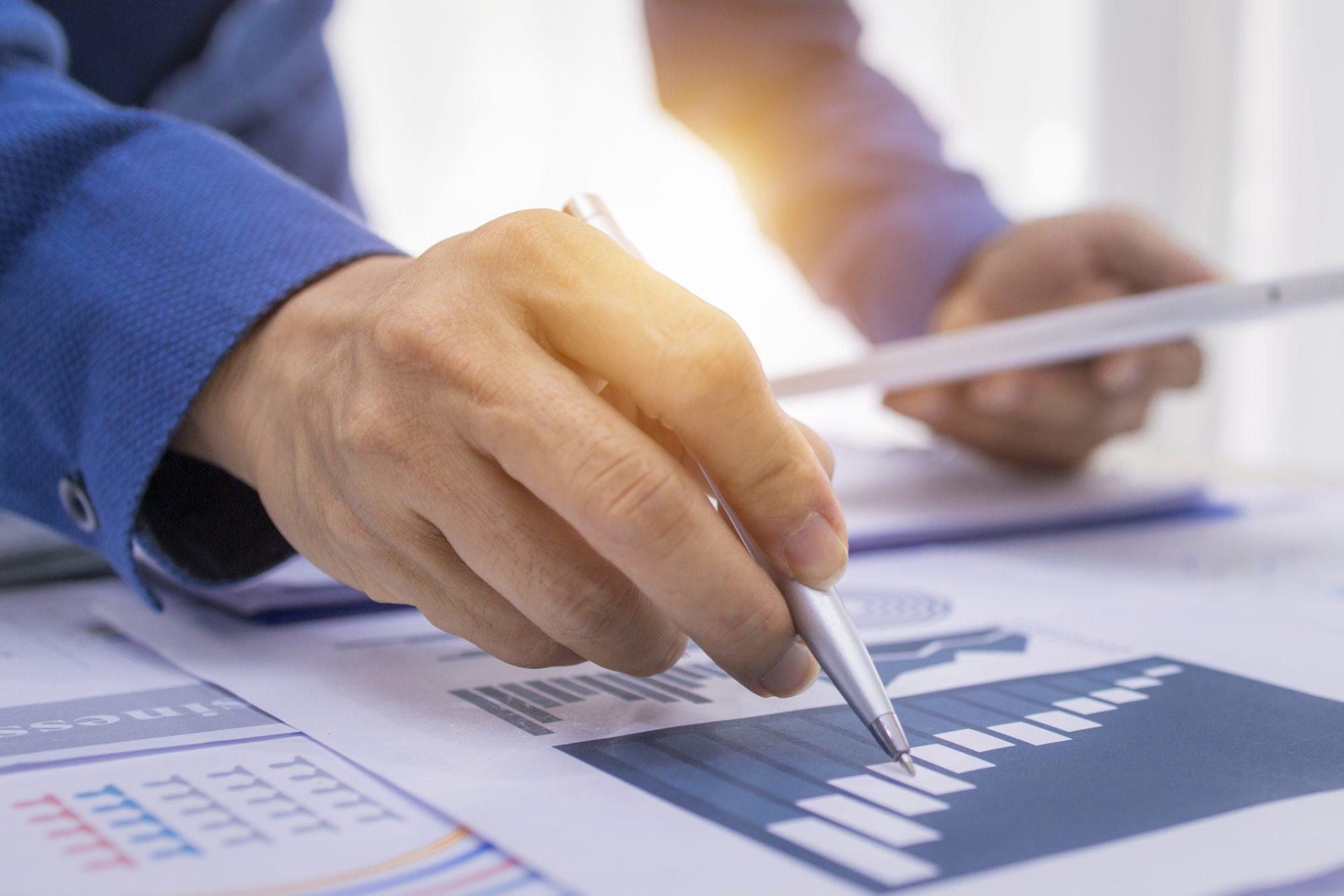"""Businessmann analysiert Charts als Metapher für den Artikel """"EZB-Leitfaden ─ Mergers & Acquisitions (M&A)"""""""