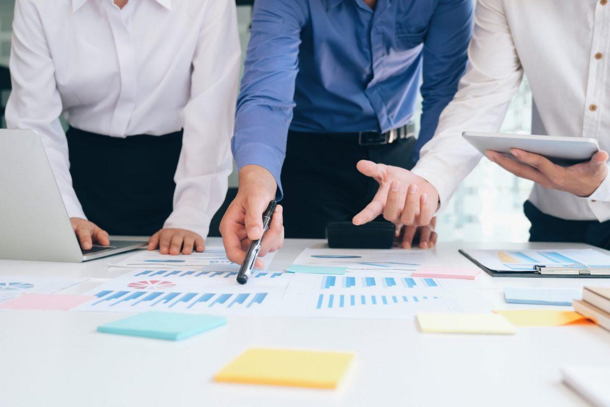 """Businessleute arbeite im Team an Daten als Metapher für den Artikel """"Zinsbuchsteuerung Integration faktischer Zinsuntergrenzen"""""""