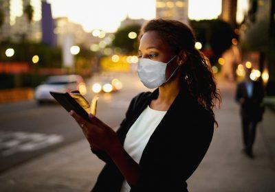 """Business-Frau mit Mund-Nasen-Maske blickt auf Smartphone-Display als Metapher für den """"zeb.market flash Q2 2020 (Issue 33 – Juli 2020)"""""""