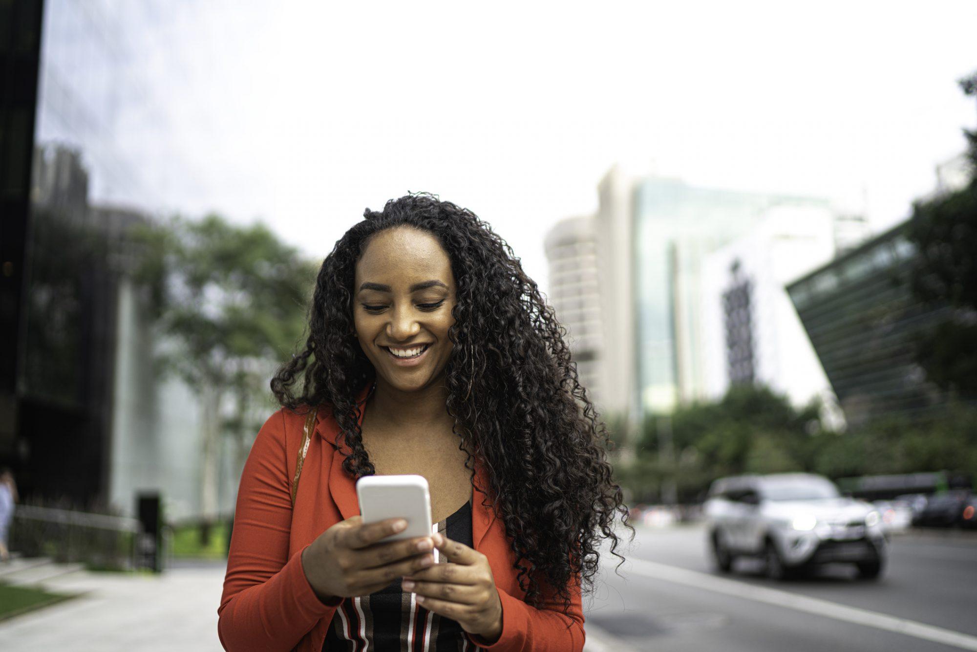 """Frau, die auf Smartphone schaut als Metapher für den Artikel """"Conversational Banking: der neue Trend in der Vermögensberatung"""""""