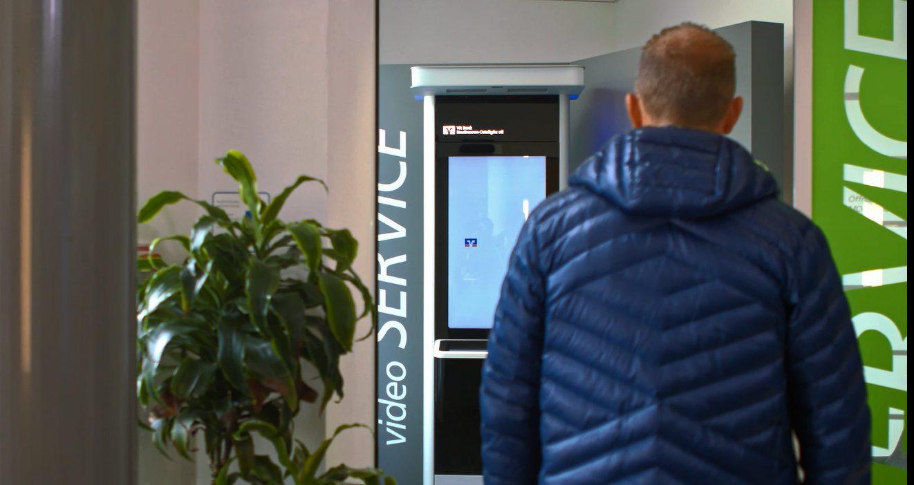 Kunde am Videoterminal der Bank Augsburg-Ostallgäu im Artikel Videoberatung – risikofreie Face-to-Face-Kommunikation in der Corona-Krise