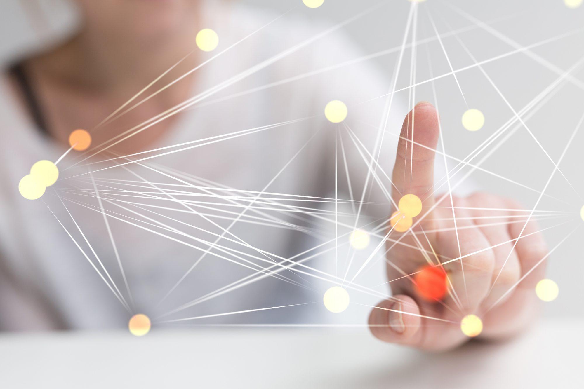 """Frau zeigt auf Netzwerksystem als Metapher für den Artikel """"Agiles Plattformmodell macht Kernbankensysteme zukunftssicher"""""""