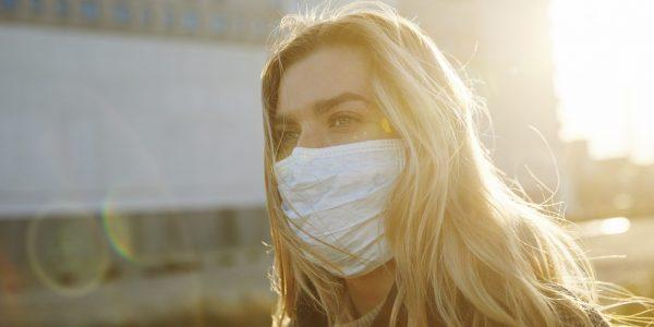 """Frau mit Mundschutz als Metapher für den Artikel """"COVID-19 wiegt weiter schwer"""""""