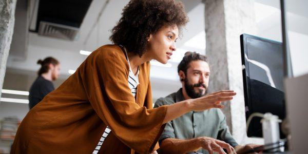 """IT-Mitarbeite blicken gespannt auf Monitor als Metapher für """"BAIT-Novelle (Konsultation 132020) – Kurzfristige Umsetzung in 2021"""""""