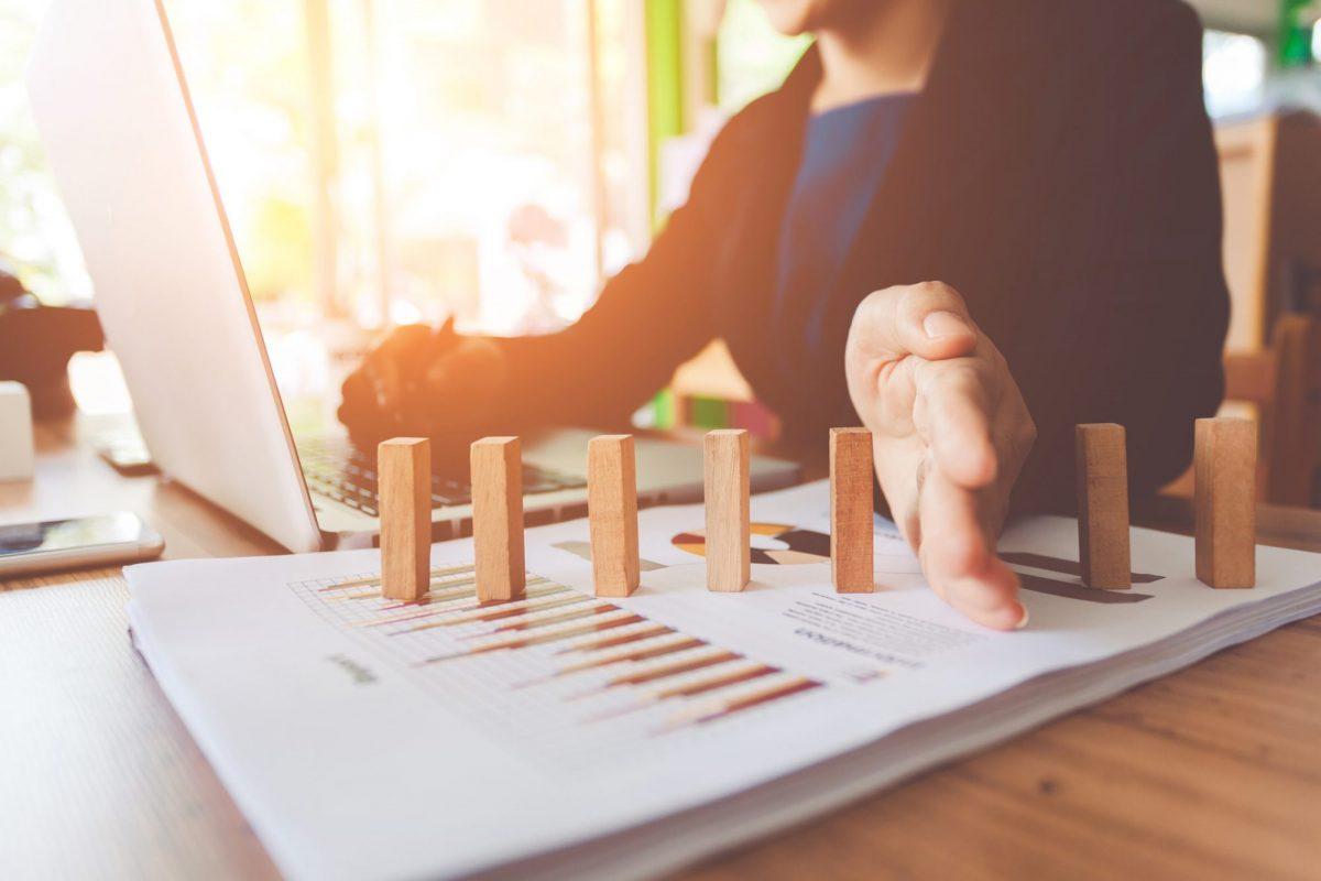"""Frau schützt Bausteine vor dem Fallen als Metapher für den Artikel """"Dynamic Risk Management Accounting: Empfehlungen"""""""