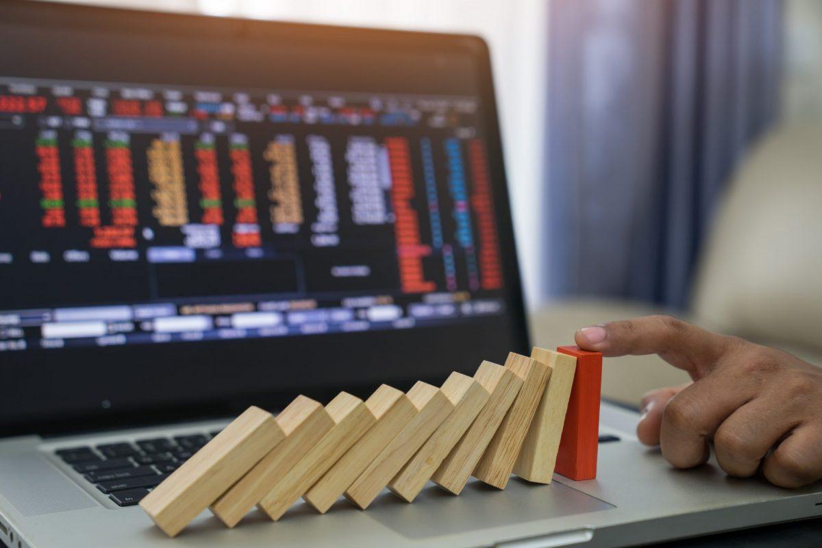 """Person verhindert Fall der Dominosteine für Bildschirm mit Kennzahlen als Metapher für """"Non Financial Risks (NFR) steuern und gleichzeitig Synergien heben"""""""