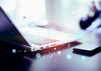 Laptop im Hintergrund von abstrakten Zahlungsströmen als Metapher für den Artikel: Geldwäscheprävention: Herausforderung Geldwäsche-Compliance