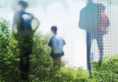 Abstrakte Personen, die Richtung grüne Stadt laufen als Metapher für Sustainable Finance (EU-Aktionsplan): MiFID II – Erweiterung um Nachhaltigkeitsaspekte