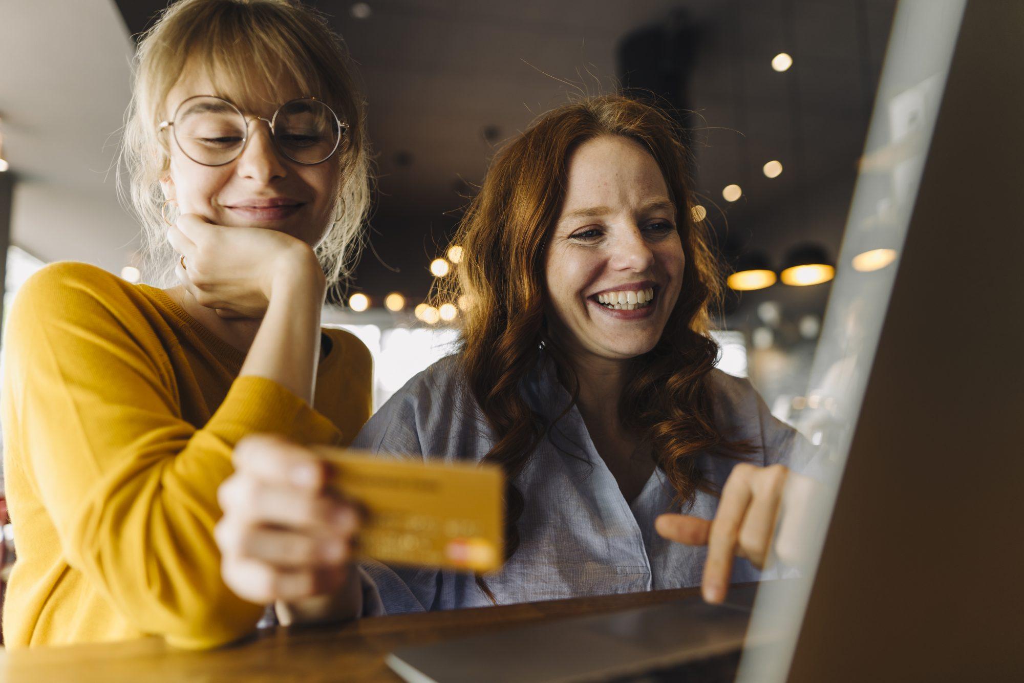 """Zwei Frauen beim Onlineshopping als Metapher für den Artikel """"Zahlungsverkehr – Geschäftsmodell als Payment-Service-Provider / Interview mit Ralf Gladis, Founder and Managing Director von Computop"""""""