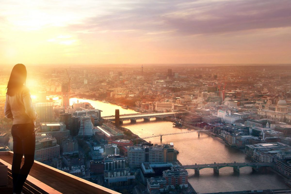 """Frau über den Dächern von London mit Blick auf Skyline als Metapher für den Artikel """"Bankensektor 2021 – erste Halbzeit ist vielversprechend"""""""