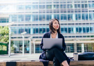 Business-Frau am Notebook als Sinnbild für Embedded Insurance mit Einfluss auf die Bankenbranche